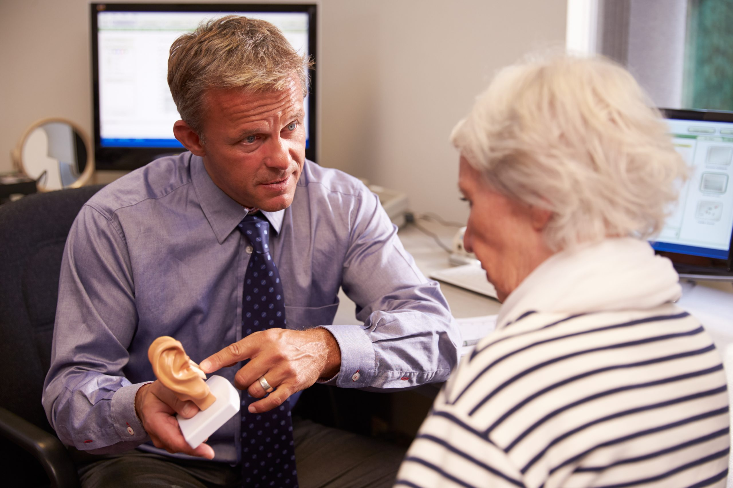 Hearing Doctor Showing Senior Female Patient Model Of Human Ear